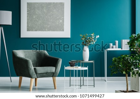 Green armchair against blue wall with silver painting in living room interior with plants #1071499427
