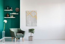 Green armchair between dandelion and plant in living room interior with copy space and grey painting