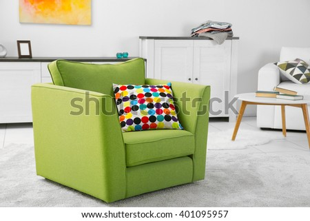 Green armchair in modern interior of living room