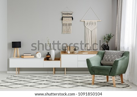 Green armchair on patterned carpet in bright living room interior with decor on the wall. Real photo