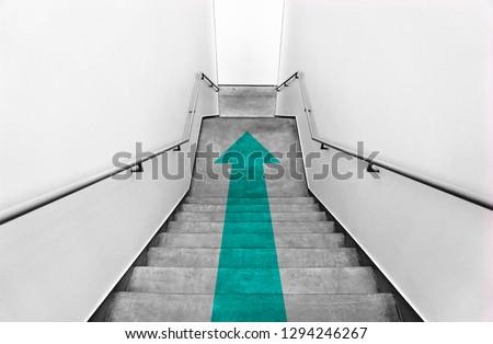Green arrow on a staircase