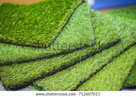 Green artificial turf rolled. Probes examples of artificial turf, floor coverings for playgrounds.