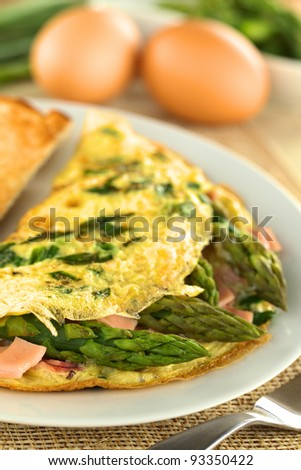 Green asparagus and ham omelet with eggs in the back (Selective Focus ...