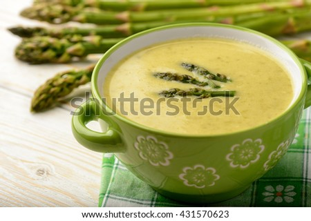 Green asparagus cream soup on wooden background. Stock photo ©