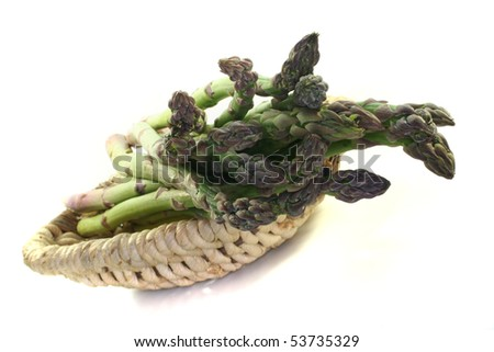 green asparagus in the basket on a white background