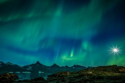 Green aurora and star burst moon over water and mountains in Greenland