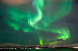 Green aurora burst in the sky of Tromso, Norway.