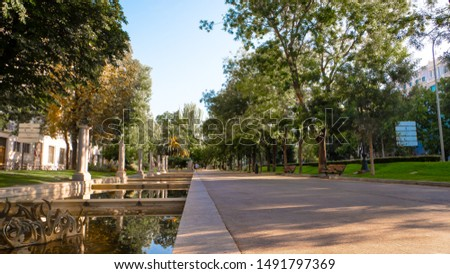 Green avenue with a pond and reflections at Paseo de la Castellana, the longest and largest avenues of Madrid, Spain at sunrise.  #1491797369