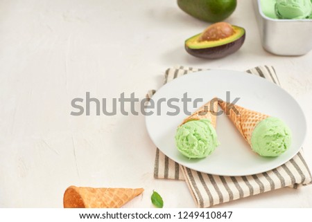 Green avocado ice cream scoops in wafle cones on white background. Copy space