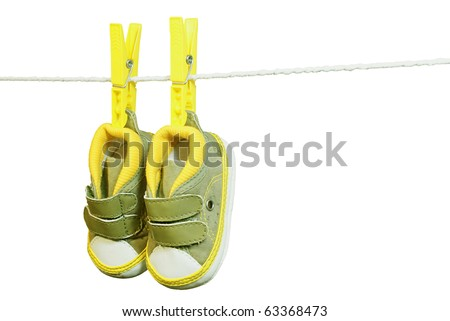 Green baby's bootee hanging on the clothesline