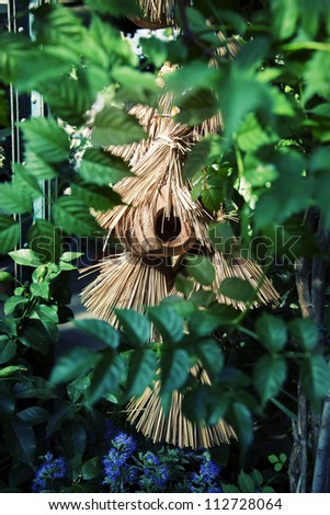 green background of straw bird house