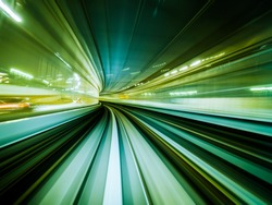 Green background of train moving through future rail tunnel bridge with blurred motion showing rapid movement.