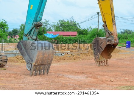 green backhoe parking in working area after work hard all day all night
