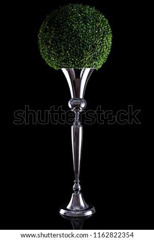 green ball of leaves in a silver vase. Decorative vase. Elegant luxury decor, black background.  #1162822354