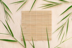 Green bamboo leaves and bamboo mat, asian style background, top view, copy space. Trendy bamboo leaves flat lay on white wooden background.
