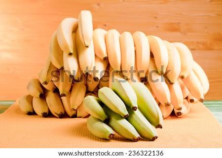 green bananas and a lot of yellow bananas on the green board on a background of yellow board
