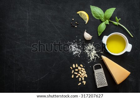 Green basil pesto - italian recipe ingredients on black chalkboard background from above. Parmesan cheese, basil leaves, pine nuts, olive oil, garlic, salt and pepper. Layout with free text space.