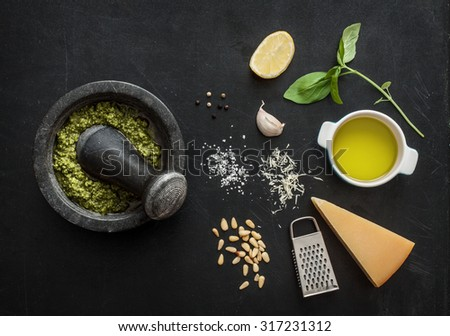 Green basil pesto - italian recipe ingredients on black chalkboard from above. Parmesan cheese, basil leaves, pine nuts, olive oil, garlic, salt, pepper and mortar.