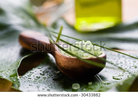 Green bath salt on wooden spoon