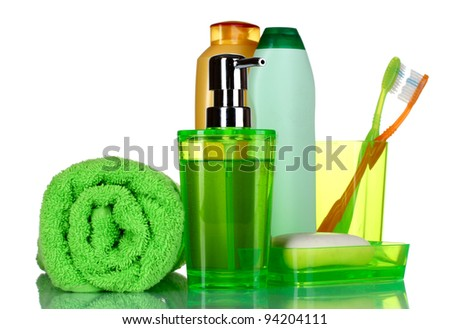 green bathroom accessories, shampoo and towel isolated on white