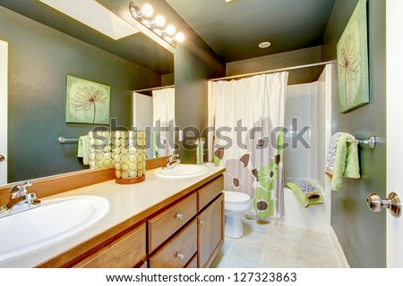 Green bathroom with wood cabinet and shower tub.