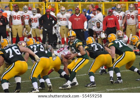 GREEN BAY, WI - NOVEMBER 22 : Green Bay Packers quarterback Aaron Rodgers takes the snap in a game at Lambeau Field against the San Francisco 49ers on November 22, 2009 in Green Bay, WI