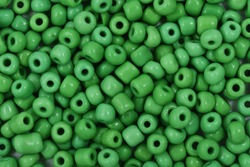Green Beads on the white background. Background or texture of beads. Close up, macro,It is used in finishing fashion clothes. make bead necklace or string of beads for woman of fashion.