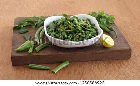Green bean curry, a South Indian Traditional and Popular Vegetarian Side Dish in a Tray on a Wooden Board