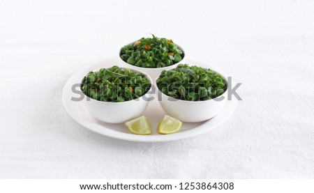 Green bean curry, a south Indian traditional and popular vegetarian side dish in three bowls on a plate with lemon slices.