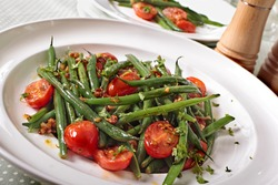 Green beans and tomato salad on white plate