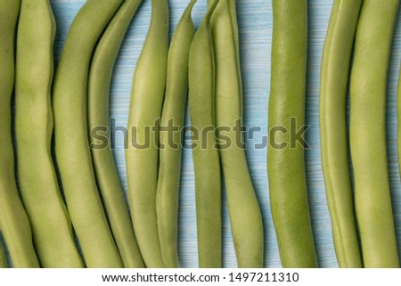 Green beans on blue wood background