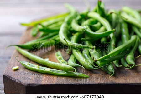 Green beans on wooden cutting board. Go green concept. Stockfoto ©