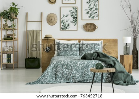 Green bedding on king-size bed in traveler's bedroom with stool, floral paintings, camera and suitcase #763452718