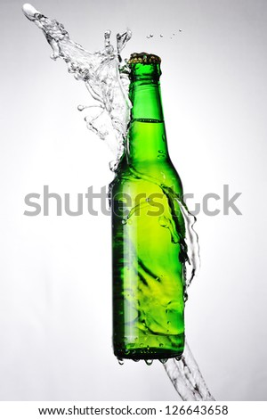 Green beer bottle and a water splash