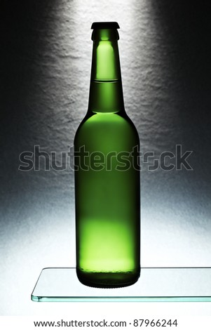 Green beer bottle in front of stone tile