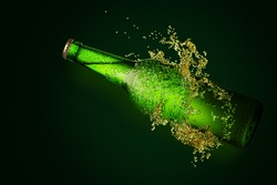 Green beer bottle with long neck in splash of beer on green background.