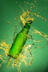 Green beer bottle with splashing liquid, freeze motion.