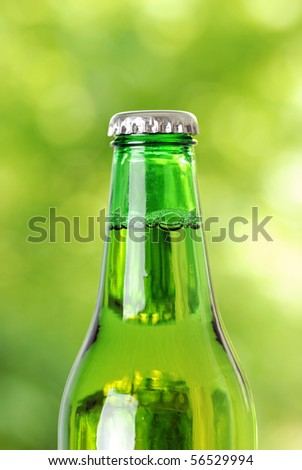 Green beer bottle with water drops on white