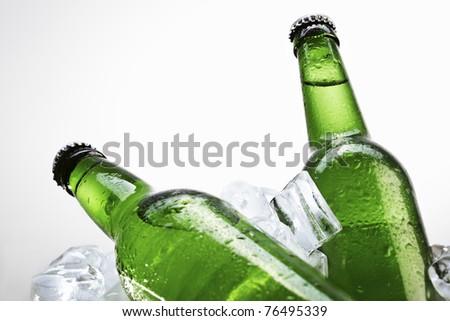 Green beer bottles on ice over white background