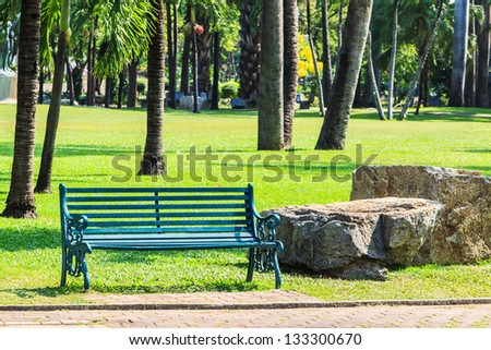 Green Bench in Palm Garden Background