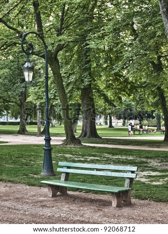 Green  bench in peaceful park in Annecy