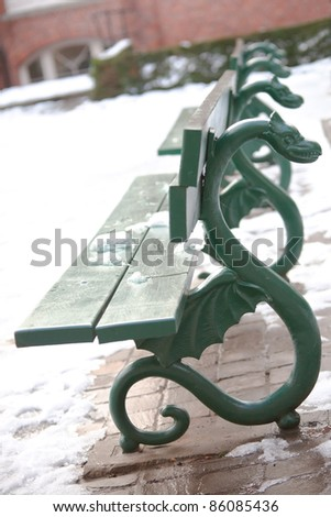 green bench with ornamental dragons at winter park in Brugge
