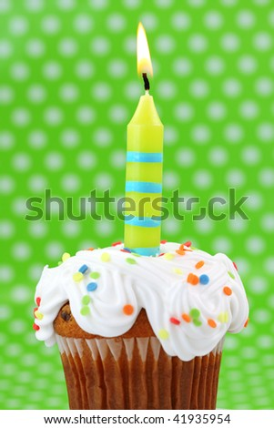Green birthday candle on green background