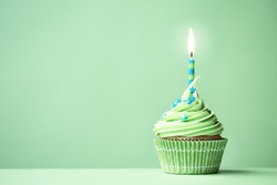 Green birthday cupcake with copy space to side