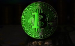 Green Bitcoin BTC coin is surrounded by a gloomy background
