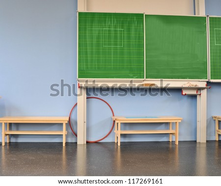 Green blackboard, furniture and floor in a school