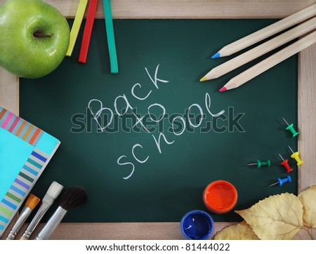 Green blackboard with brushes, book, apple and pencils