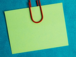 green blank note pinned to a blue notice board with a paper clip.