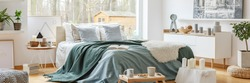 Green blanket on a cozy, double bed by a large window in a scandinavian style bedroom interior with a view at a forest