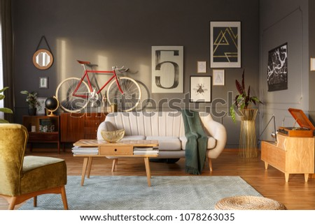 Green blanket on a sofa in vintage living room interior with wooden furniture and red bike